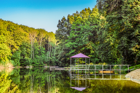 Lake in a forest with a gazebo and small pier for pleasure pedal catamaran on the lake shore. Summer landscape.