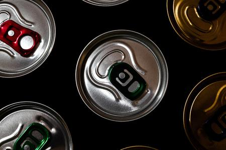 Metal beer cans in the dark black background. Various aluminum beverage cans. Top view close-up. 版權商用圖片