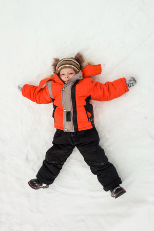 Happy little boy child laying on snow and making snow-angel