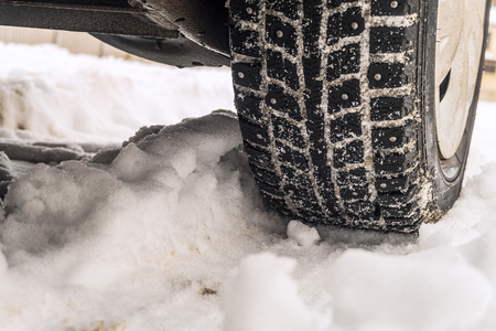 Wheel close-up on a slippery snowy winter road. Winter studded tires for snowy road.