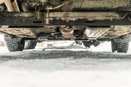 Bottom of the car with studded tires on a winter snowy road. Road clearance. Chassis close-up with limited depth of field. Stockfoto