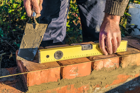 Bricklayer checks the horizontal level of brick masonry wall with a bubble level. Construction worker.