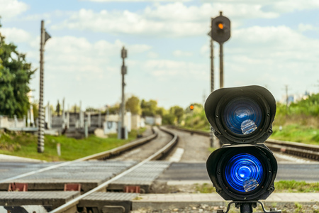 Railway traffic light with a blue standard signal. Semaphore on railroad crossing on a blurred background. Railway Infrastructure. Selective focus.