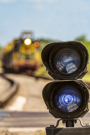 Railway traffic light with a blue standard signal. Railway crossing with semaphore and locomotive train on a blurred background. Selective focus.