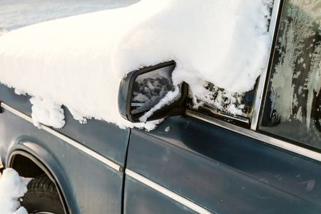 Classic car in snowdrift. Snow-covered car blocked after heavy snowstorm.
