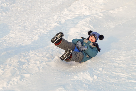 Boy rides on an ice-boat from a snow slide. Sledding snow saucer - winter childrens fun. Stock Photo