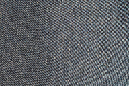 Gray blue denim texture. Dark jeans close-up.