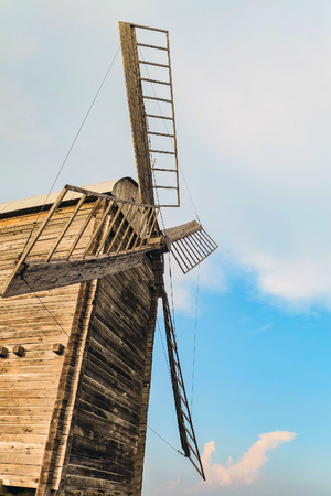 Ancient wooden flour windmill. Old agriculture architecture.