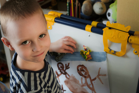 Little boy shows off his drawing fixed on magnetic drawing board 스톡 콘텐츠