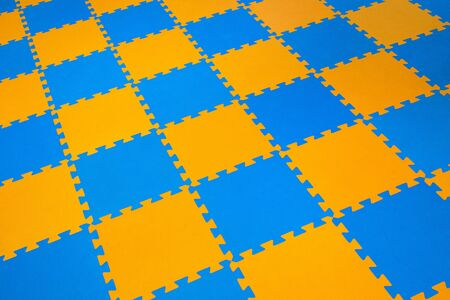 Rubber orange-blue colored floor puzzle. Horizontal layout perspective. Flooring indoors playground.
