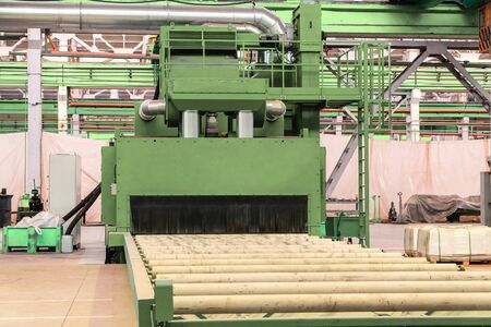 Shot blasting machine with roller table. Roll blasting machine on industrial plant shop.
