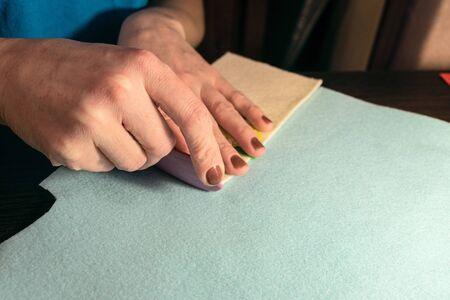 Sewing master makes handicraft of fabric. Felt products. Cutting with a mark of soap.