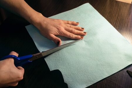 Cutting fabric with scissors. Felt products. Sewing master makes crafts from the fabric.