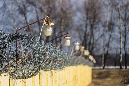 Barbed wire on a concrete fence with light lamps. Day view with limited depth of field and blurred background.
