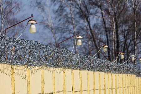 Barbed wire on a concrete fence with light lamps. Day view with limited depth of field.
