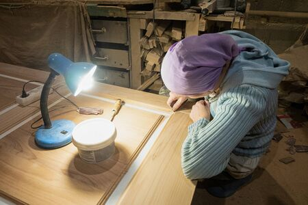 Woman joiner cleans and putty spats surface of door leaf in the carpentry shop. Woman working in the male profession.