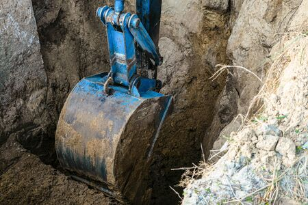 Bucket excavator digs soil at construction site Standard-Bild