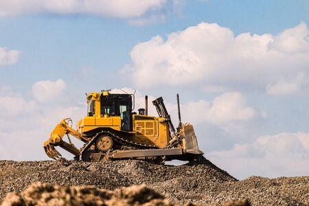 Yellow motorized bulldozer raking rubble piles. Road building industry.