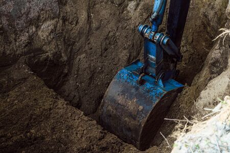 Bucket excavator digs soil at construction site. Construction hydraulic equipment.