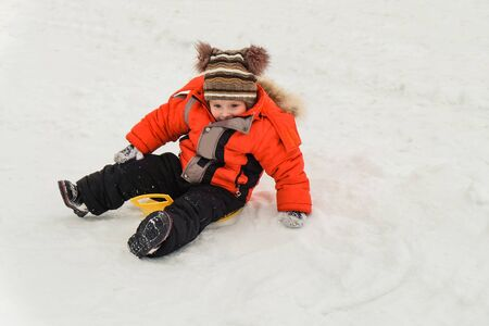 Little boy rides on an ice-boat from a snow slide. Sledding snow saucer - winter childrens fun. Winter activity. Stok Fotoğraf