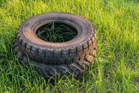 Car rubber tires thrown into a stack on green grass. Environmental pollution. Reklamní fotografie