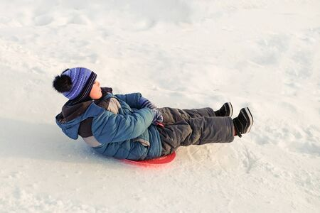 Child boy rides on an ice-boat from a snow slide. Sledding snow saucer. Stok Fotoğraf