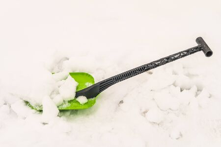 Compact steel snow shovel with plastic handle. Winter motorist tool in the snow. Stock Photo