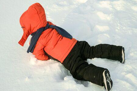 Little boy fell in the snow on a winter walk