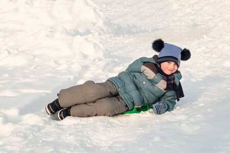 Child slid down a snow slide and is happy lies on an ice-boat. Sledding from a snow plate. Stok Fotoğraf