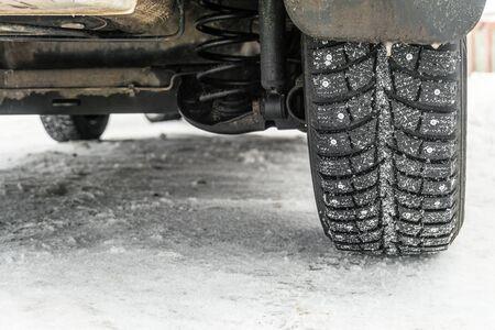 Wheel on a slippery snowy winter road. Car back wheel on a snowy winter.
