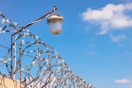 Barbed wire on a fence with light lamp. Barbwire on a blue sky background.