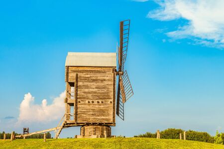 Ancient wooden flour windmill. Side view. Old agriculture architecture. Stock Photo