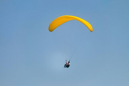 Flight on a yellow paraglider in blue sky