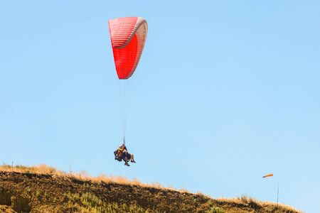 Tourist pair flight on a red paraglider in blue sky above the earth
