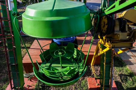 Ferris wheel drive mechanism and green steel classic cabin. Gear wheel with chain drive at the amusement park.