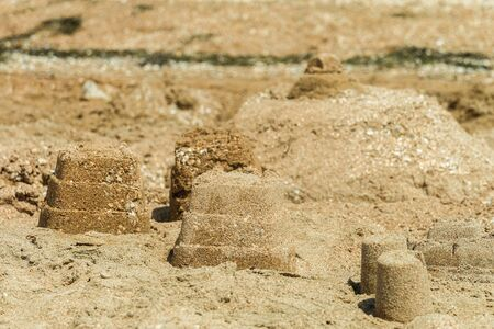 Simple sand towers and castle on a sunny sandy sea beach