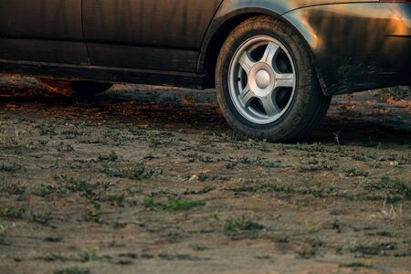 Black car stands on dry clay soil with sparse stunted vegetation Stockfoto