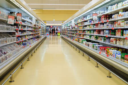 Belgorod, Russia - July 14, 2019: Long passage with food products for sale, exposed in refrigerators and shelves in Auchan supermarket. Dairy department.
