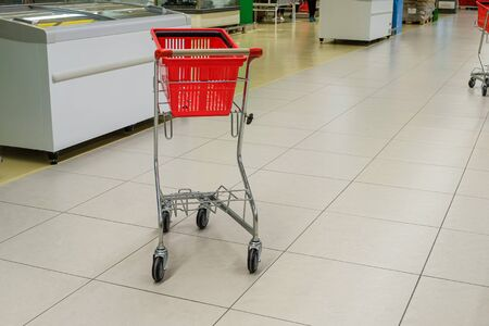 Empty red grocery basket with cart in supermarket aisle 版權商用圖片