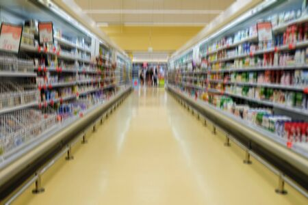 Long passage with food products for sale, exposed in refrigerators and shelves in supermarket. Blurred moving effect.