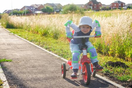 Small boy rides a tricycle on a track in the suburb 版權商用圖片