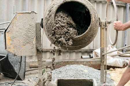 Concrete spills out of the tank. Concrete mixer in blurry motion mixes expanded clay with cement.