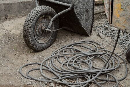 Unicycle wheelbarrow and electric cable at the construction site