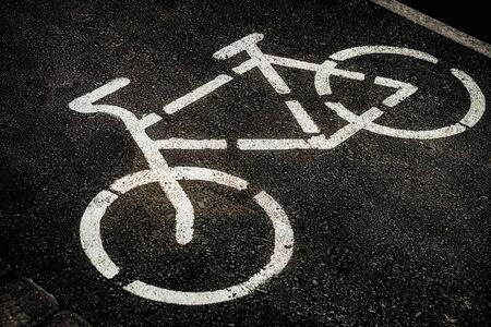 Bicycle path sign on dark asphalt. Bicycle painted in white paint on a black road. Foto de archivo