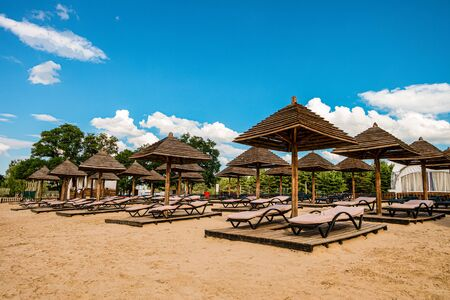 Brown wooden loungers and umbrellas on empty sandy beach. Rows resting places in the failed tourist season.