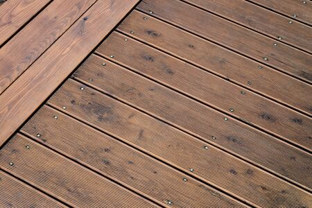 Natural outdoors wooden board floor. Brown floor fixed with screws pins.