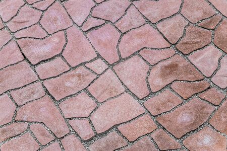 Pavement covering. Footpath paved with red tiled stone. Close-up.
