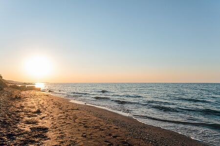 Empty sandy sea beach at sunset. Evening sea landscape with low sun on horizon. Krasnodar region, Russia.