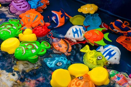 Childrens plastic colorful fish toys in the pool for playing in the fishing Foto de archivo