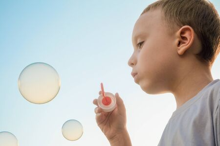 Boy blowing soap bubbles on the evening blue sky background. Side view.